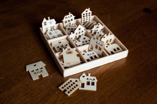 "Tiny laser-cut wood houses. These are about 1 1/8"" in height."