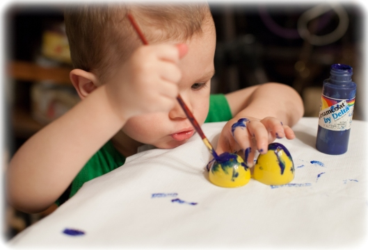 Two year old Grandson paints an egg.