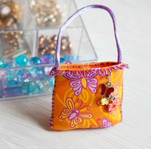 Tiny ribbon purse with charm dangle.