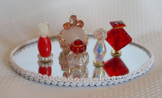 Miniature perfume bottles made from beads. This dresser tray is a mirror with trim glued around the edge.