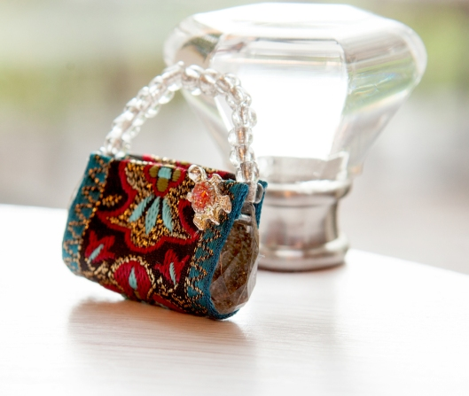 I used a tiny turtle from a pierced earring to embellish this miniature clutch purse.