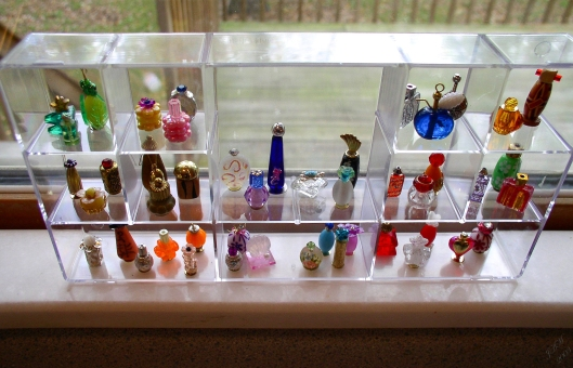 A small plastic organizer with the lid removed made an elegant faux glass shelf unit for the miniature bead bottles.