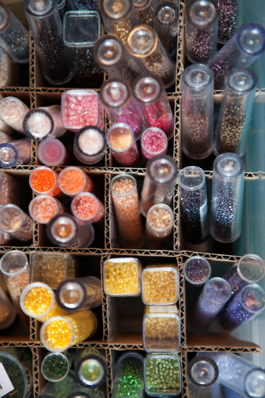 Seed beads, mostly size 11, including Aiko and Delicas, fill a bin with color.