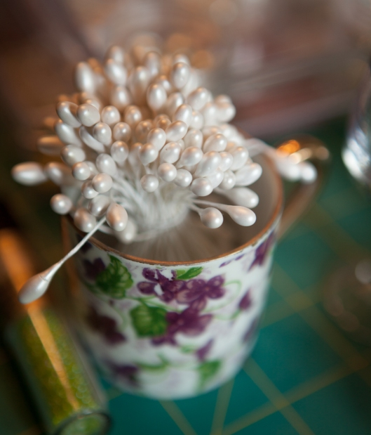 A small child's teacup holds white stamens.