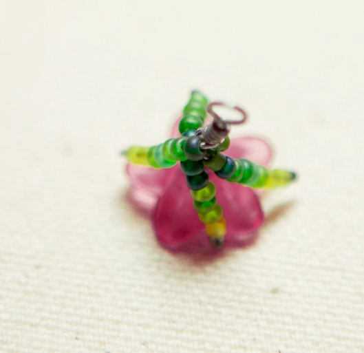 The calyx is made of two tiny wires of green beads, twisted around a central wire.