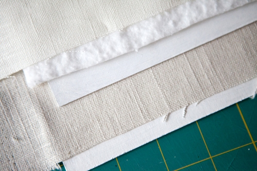 The materials used to make the book cover: Ivory linen over batting over chip board, which is then glued to a larger piece of chip board covered with natural linen.