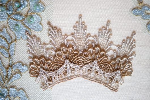 The crown is carefully positioned on the book cover and pressed down around all edges.