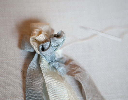 The ribbon loops are sewn to the back of the ribbon rose buds.