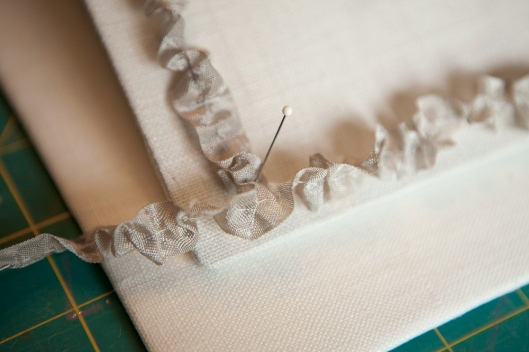 Seam binding tape is gathered down the middle and the pinned to the cover to check for size and adjust ruffles.