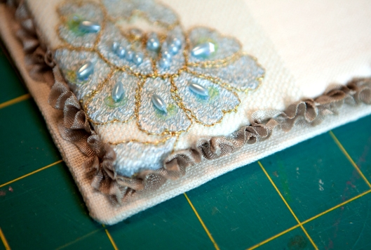 The top of the cover is glued on the larger linen-covered board. Then while the glue is still wet, the ruffled seam binding tape is pushed into glue.