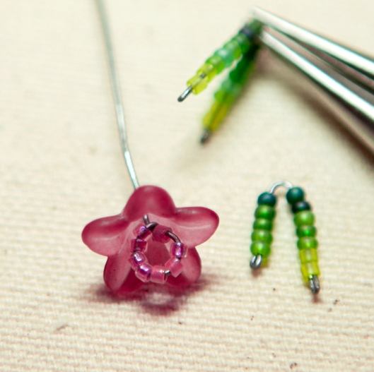 Insert the flower center into a flower bead.  Slide the green beads apart at the center and bend the calyx wires in half.