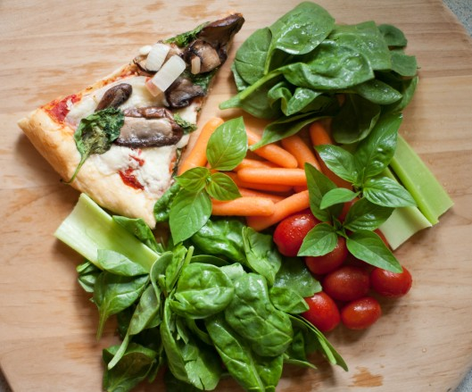 Pizza Salad Ingredients: leftover Spinach Mushroom Pizza, grape tomatoes, celery sticks, carrots, spinach, Thai basil and Lime basil leaves.