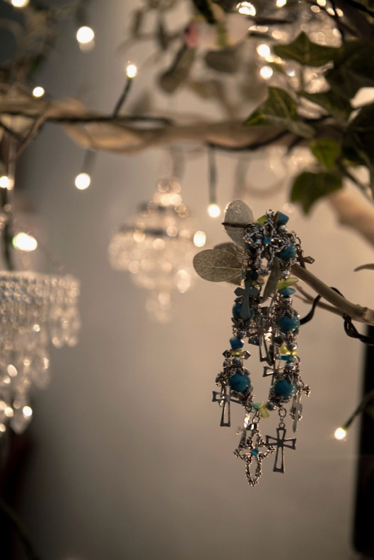 Chandelier ornaments and a bracelet hang from an artificial tree to light my new office space.