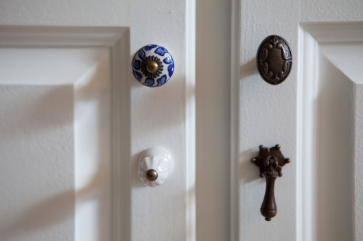 Mismatched knobs used in place of cabinet handles.