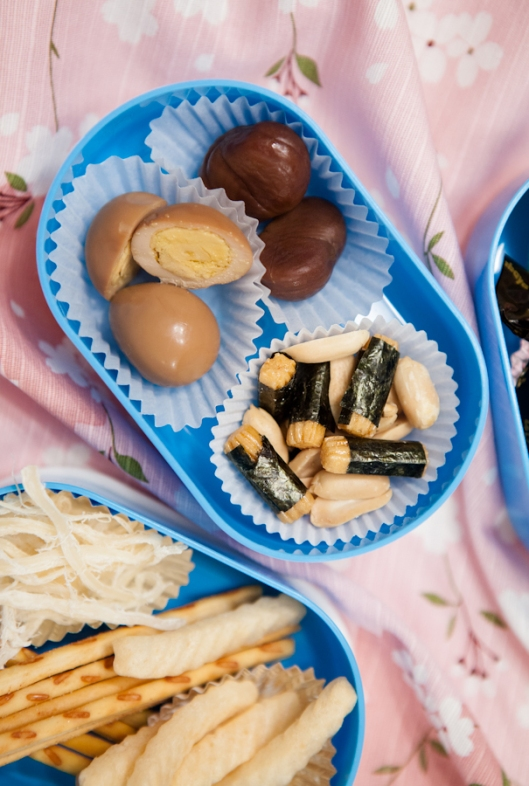 Quail eggs on the upper left, preserved chestnuts at upper right, crispy nori-wrapped snacks with peanuts.