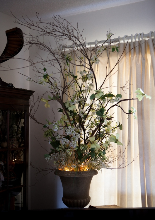 The same bare branches now share the space with artificial dogwood and greens. The lights were taken off the branches and placed in the vase for ambience.