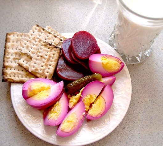 Two pickled eggs with beets, a sweet pickle and matzoh.