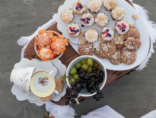 On the top tray: Vanilla Bean cakes filled with Blueberry Pomegranate Jam and topped with Coconut Cream Glaze, toasted coconut & macadamias, sugared lavender and rose petals. On the bottom tray, Spice Madeleines sprinkled with vanilla pearls. On the dessert plates under the tea cups: Lavender Lemon Shortbread.