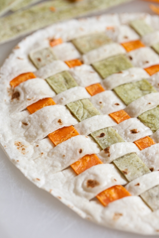 Green and orange tortilla strips are woven through the slits in a white flour tortilla.