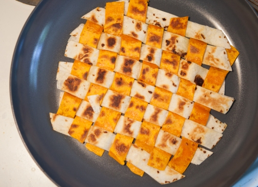 The woven tortilla mat is lightly toasted on both sides over medium heat in a skillet.