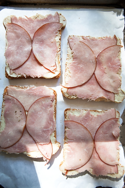 Tear two round ham slices in half to fit a square piece of bread.